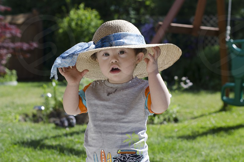 Little boy caught trying on Grandma's sun hat photo