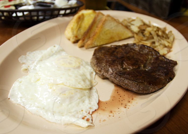 Breakfast sirloin steak and fried eggs with toast and hashbrowns photo