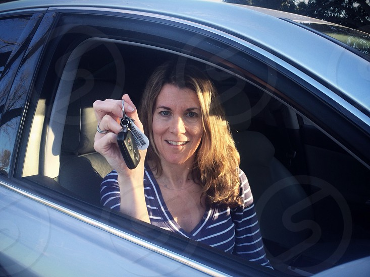 Woman in car holding keys. Confidently looking ahead photo