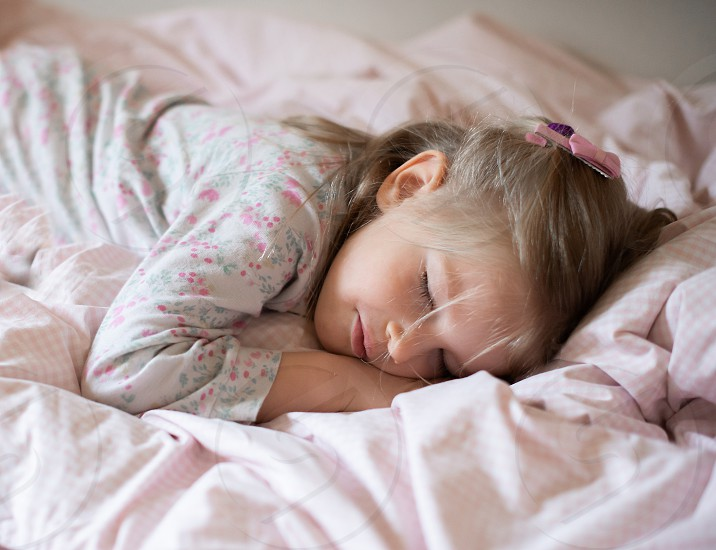 Adorable little child girl sleeping in the bed. photo