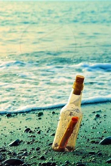 clear glass bottle with cork lid on the beach photo