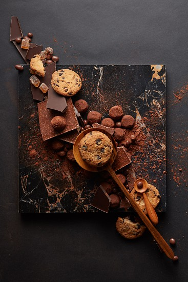 frame of homemade cookies with chocolates and candies on the marble tray and a black background photo