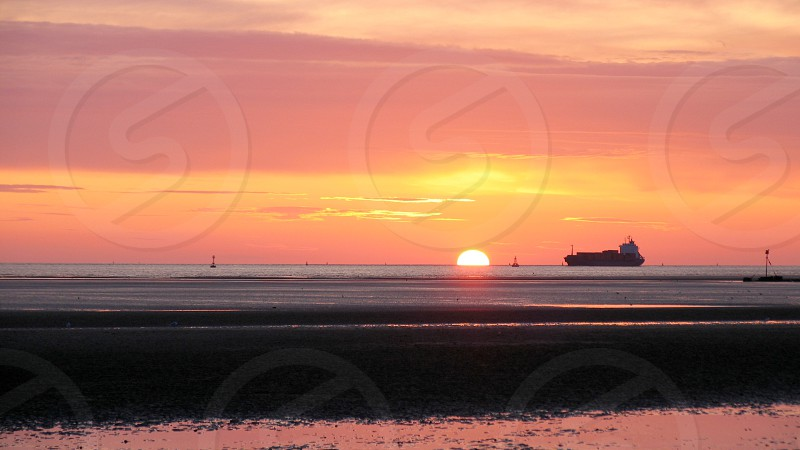 Ship on horizon at sunset photo