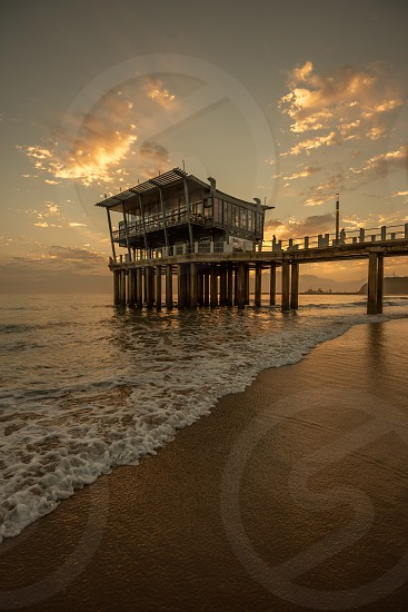 Moyos Pier is silhouetted against the sky at sunrise at South Beach Durban South Africa. photo