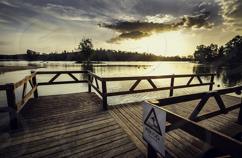 Pier with wooden balustrade illuminated by the sunset sun with warning sign to bathe and the sky covered with clouds photo