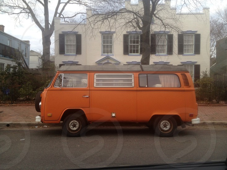 orange van parked in front of a white painted house photo
