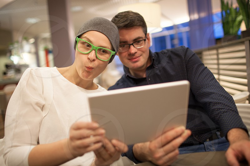 Young man and woman in glasses wriggle while making selfie sitting in the restaurant photo