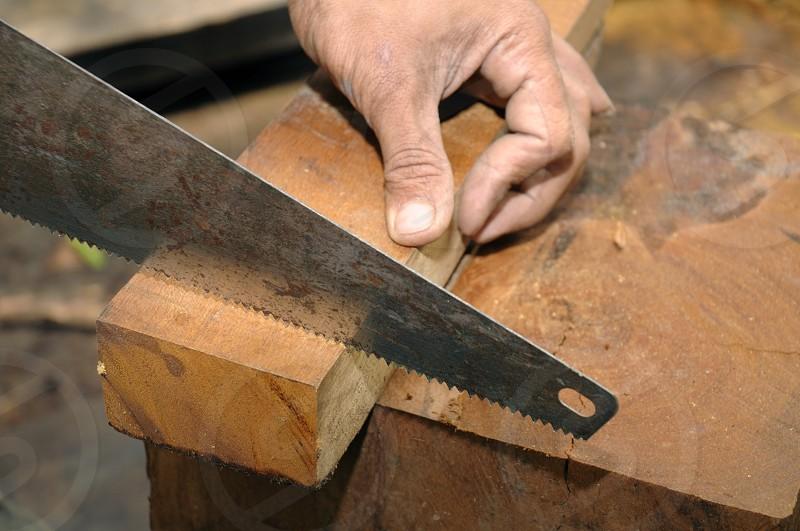Closeup of carpenter sawing wood block. photo