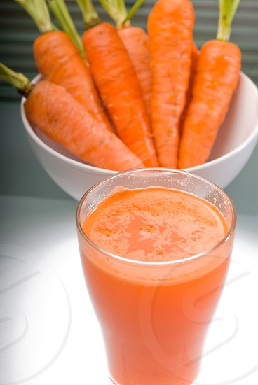 fresh and healty carrot juice unfiltered over a light table photo