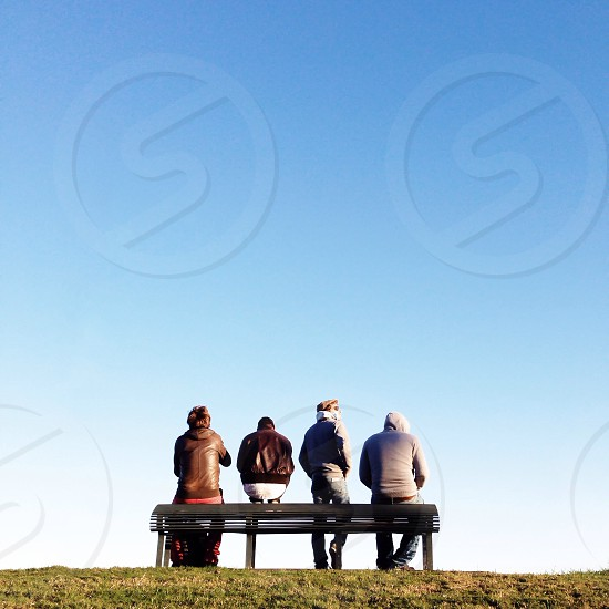four people sitting on bench under blue sky photo