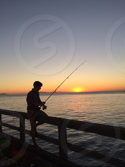 silhouette of person on dock fishing in ocean under orange sunset photo