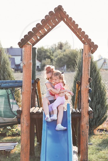 Teenage girl playing with her younger sister in a home playground in a backyard. Happy smiling sisters having fun on a slide together on summer day. Real people authentic situations photo