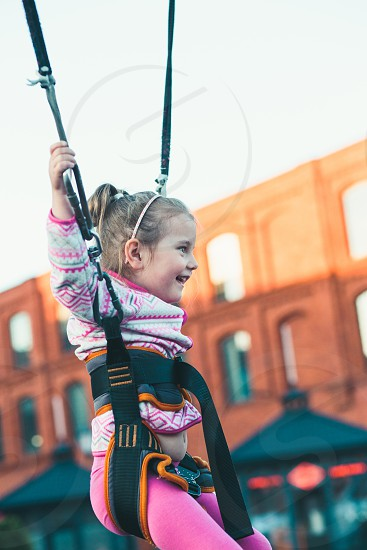 Little adorable smiling girl jumping on trampoline having fun at funfair photo