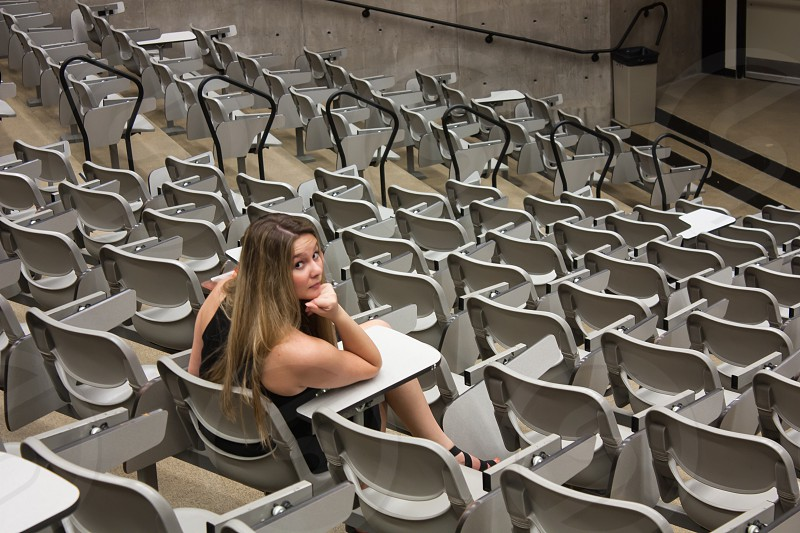 A female college student sits alone in a lecture hall contemplating her time spent here photo