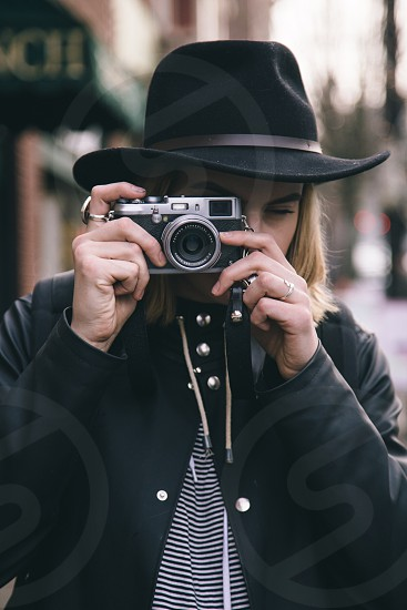 Young woman photographing in fashionable hat.  photo