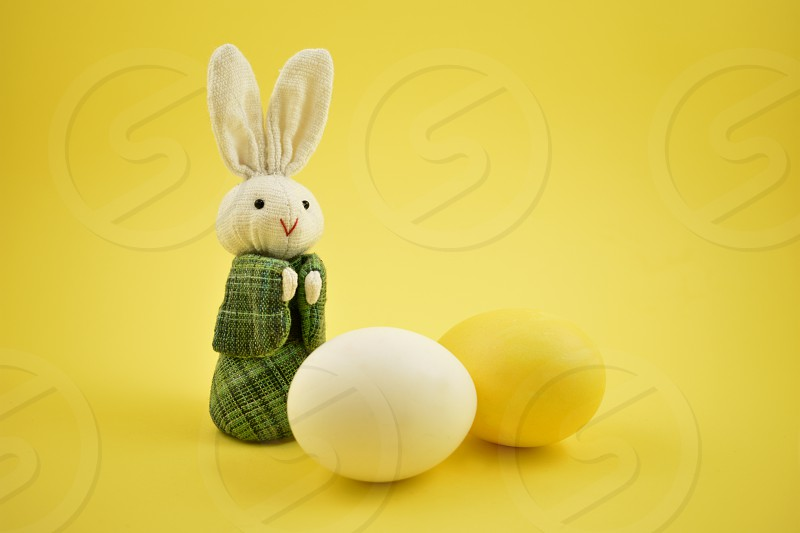 White rabbit toy. Easter bunny on a yellow background. Easter rabbit with egg. Spring decoration images. Easter concept photo