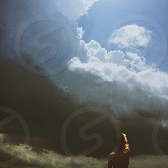 man standing pointing blue and black skies photo
