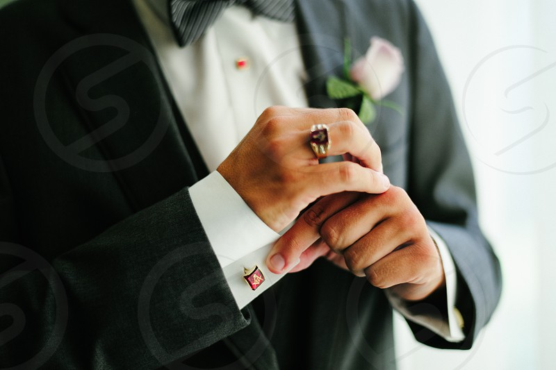 man in black tuxedo fixing his cufflink with white rose in his pocket photo