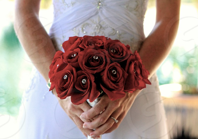 woman in white beaded wedding dress holding red rose bouquet with white diamonds in both hands photo
