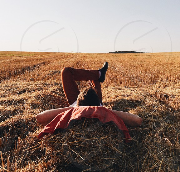 man lying over brown hay on ground under clear skies during daytime photo