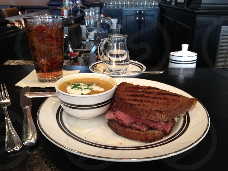 Reuben sandwich with bowl of soup and glass of tea on black bar photo