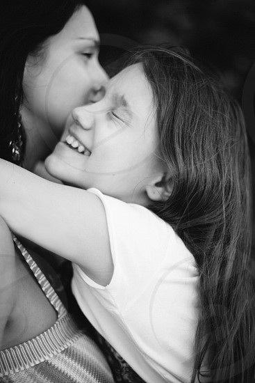 grayscale photography of mother and daughter while hugging photo