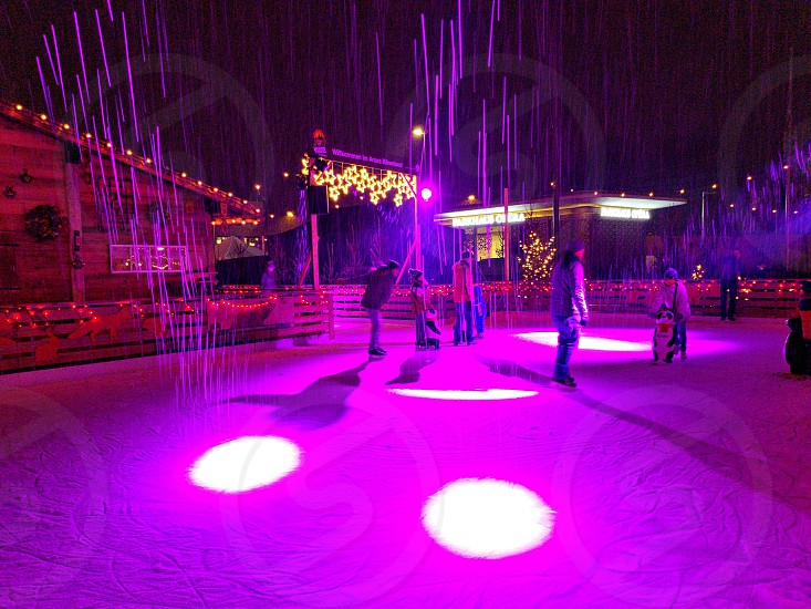 people standing on floor with pink light effects photo