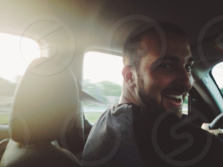 man in black and grey shirt smiling inside the car photo