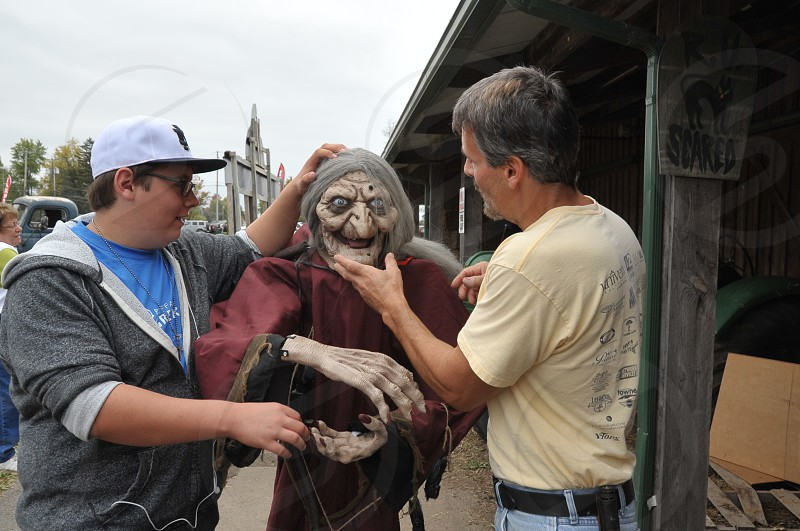 Son and his Dad choosing scary witch decoration for Halloween at a Fall Festival photo