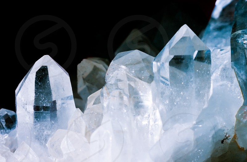 Cluster of rock crystals or pure quartz a clear macrocrystalline variety of silica (SiO2) isolated on black background. This gemstone is said to have strong healing power. Birthstone for April photo