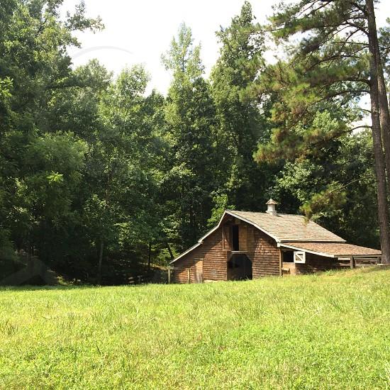 brown barn across green grass field photo