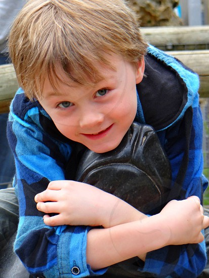 Boy hugging a seal with blue shirt.  photo