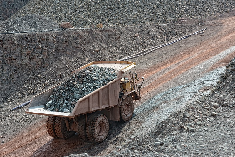 dumper truck with loaded stones driving along in a quarry. mining industry. photo