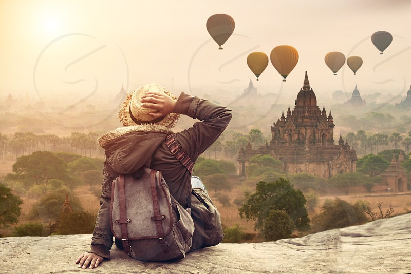 Myanmar Young hipster woman traveller backpacker sitting watch Beautiful landscape Bagan Mandalay ancient pagoda in Bagan Mandalay Myanmar. Beautiful landmark of Asia. photo