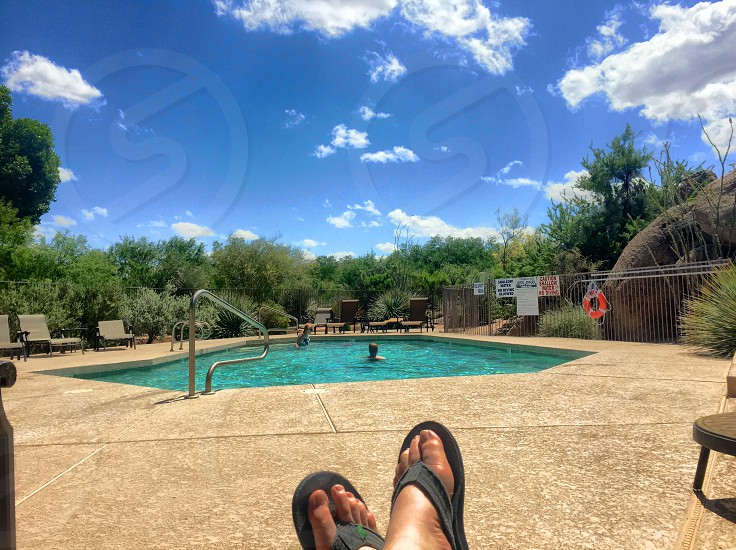 person's feet with gray slippers with swimming pool view photo