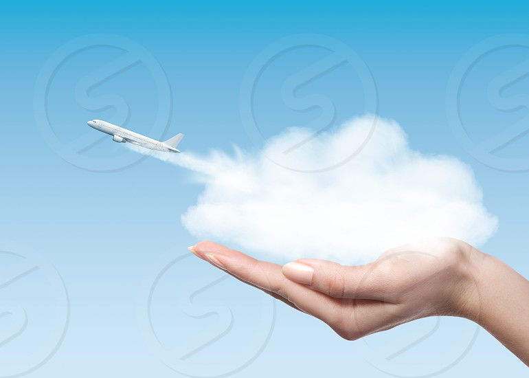 Female holding clounds in hands from which plane taking off into air. Business concept. photo