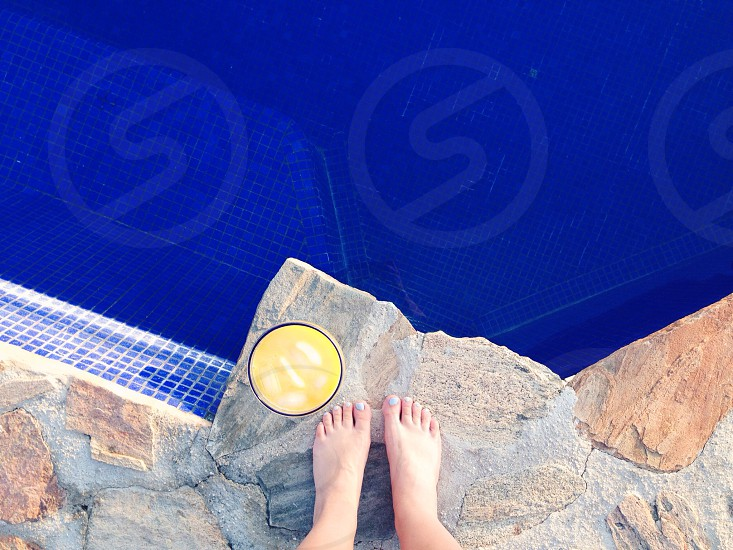 person standing near clear highball glass of juice on pool side photo