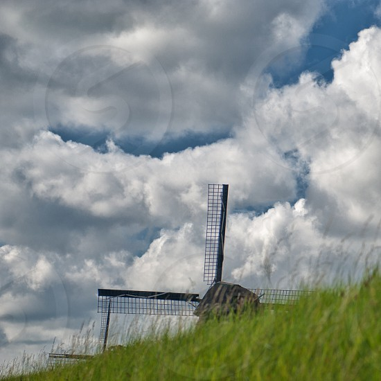 windmill by green grass field  under white cloudy blue sky during daytime photo