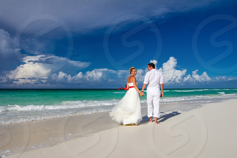 Just married couple walking on the beach photo