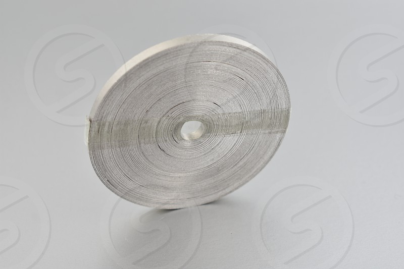 Magnesium ribbon. Laboratory accessories. Laboratory equipment on a silver background. A coil of magnesium ribbon. Chemical element photo