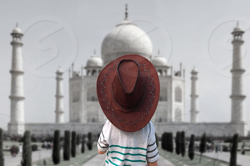 person in brown cowboy hat standing in front of tadj mahal painting photo