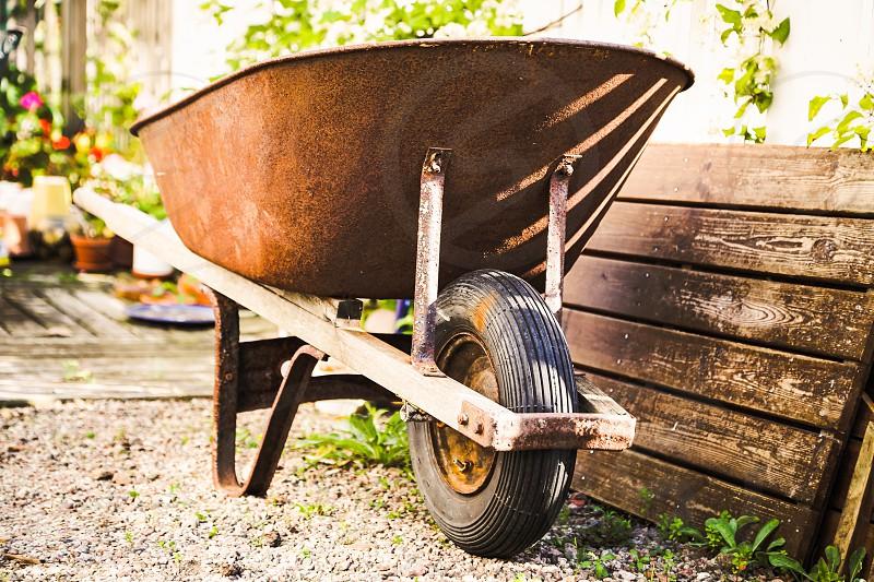 brown metal wheelbarrow beside flipped brown outdoor bench photo