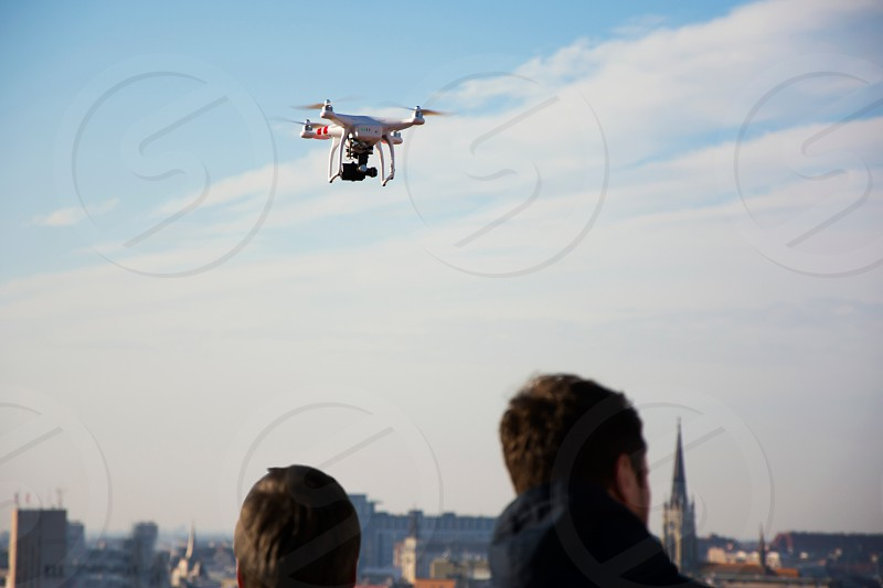 Two guys managing their drone while filming themselves above city photo
