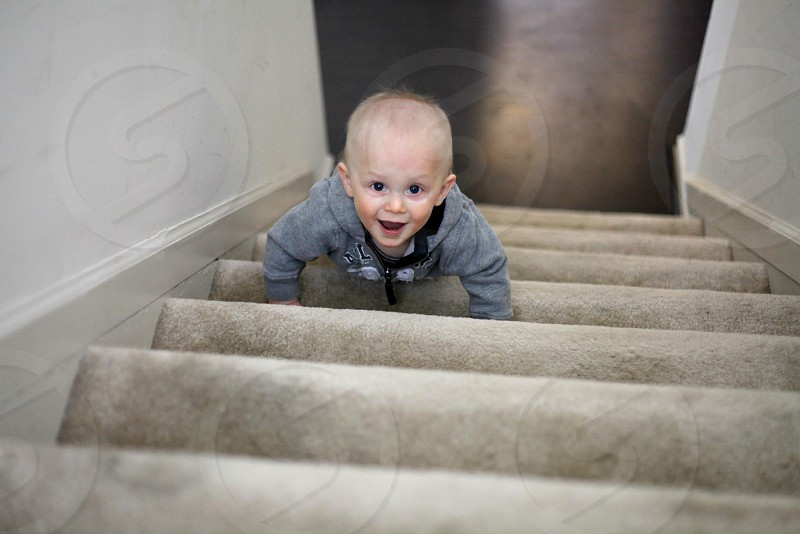 child in gray hoodie climbing up on gray suede stairs photo