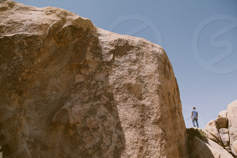 person standing on brown rock formation photo
