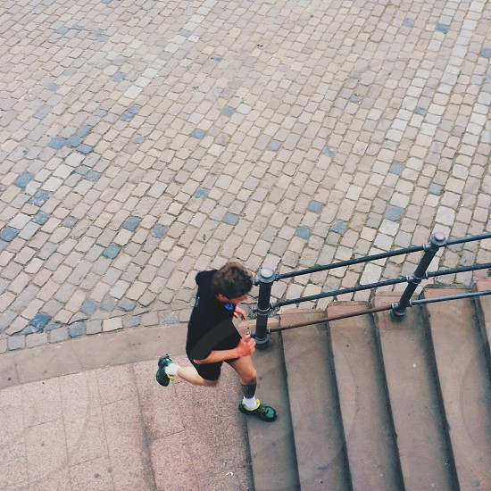 man in black t shirt running up the stairs photo
