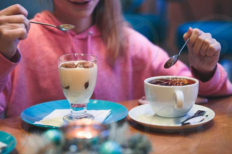 Girl eating a dessert and drinking a tea in coffee shop. Candid people real moments authentic situations photo
