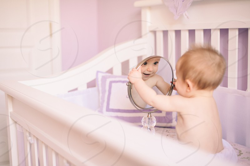 baby in the crib looking in the mirror photo