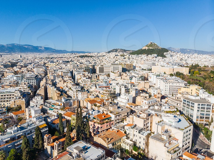 City views of day time with acropolis on a hill at the horizon Athens Greece photo