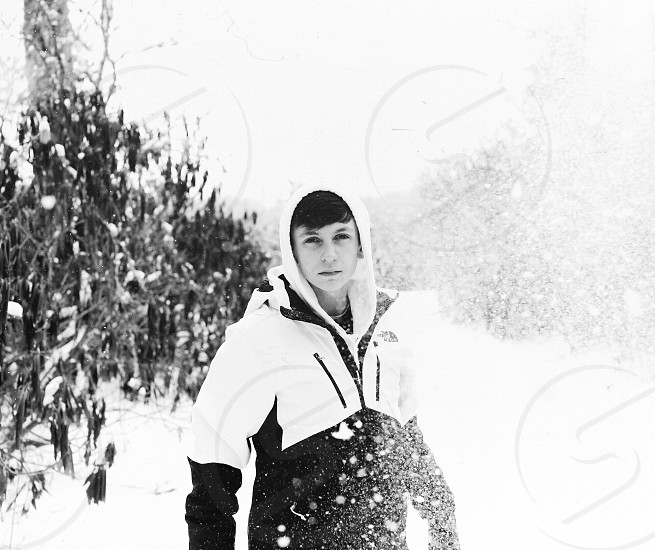 man in zip hoodie standing on snow in greyscale photography photo